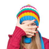 Young woman wearing colorful hat hiding behind her hand Royalty Free Stock Images