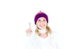 Young woman wearing a colorful hat pointing upward Stock Image