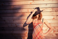 Young woman wearing cowboy hat by a cabin Stock Images