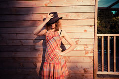 Young woman wearing cowboy hat by a cabin Stock Image