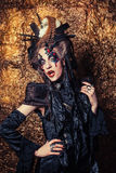 Young  woman wearing dark costume. Bright make up and smoke-  halloween theme. Stock Photo