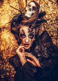 Young  woman wearing dark costume. Bright make up and smoke-  halloween theme. Royalty Free Stock Images