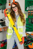 Young woman wearing denim jumpsuit and glasses with long hair holding in hands spirit level and smiling. Stock Image