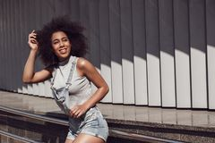 Young woman wearing overall shorts in the city street near shutter wall leaning on handrails looking aside joyful stock image