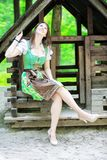 Young woman wearing a dirndl sitting at wooden lodge stock image