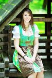 Young woman wearing a dirndl sitting at wooden lodge royalty free stock photos