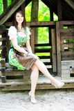 Young woman wearing a dirndl sitting at wooden lodge royalty free stock image