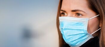 Free Young Woman Wearing Disposable Blue Virus Face Mouth Nose Mask, Closeup Portrait - Wide Banner With Space For Text Left Side. Royalty Free Stock Photos - 178788348