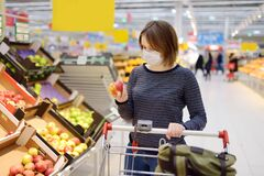 Free Young Woman Wearing Disposable Medical Mask Shopping In Supermarket During Coronavirus Pneumonia Outbreak Stock Photography - 174896642