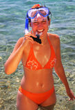 Young woman wearing diving goggles. Young woman in orange bikini with diving goggles Royalty Free Stock Photo