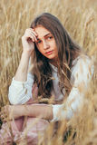Young woman wearing dress sitting in field with wheat Royalty Free Stock Photos