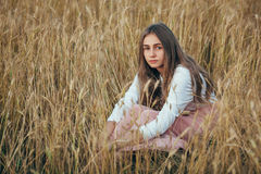 Young woman wearing dress sitting in field with wheat Royalty Free Stock Photography