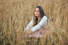 Young woman wearing dress sitting in field with wheat Royalty Free Stock Photo