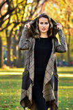 Young woman wearing elegant design coat, posing in the autumn park. Beautiful blonde young woman wearing elegant design coat, posing in the autumn park stock photo