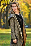 Young woman wearing elegant design coat, posing in the autumn park. Beautiful blonde young woman wearing elegant design coat, posing in the autumn park royalty free stock photos