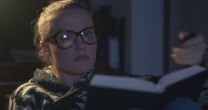 Young woman wearing eye glasses reading a book in the evening. stock video
