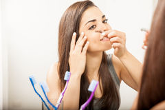 Young woman wearing false eyelashes. Pretty young brunette putting a false eyelash while standing in front of a mirror in a bathroom stock image