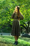 Young woman wearing fashionable dress walking in park during autumn weather. Young woman wearing fashionable dress walking in park during autumn weather Stock Photography
