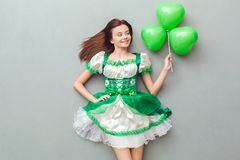 Young woman in a festive dress saint patrick`s day top view looking at balloon. Young woman wearing a festive dress saint patrick`s day  on grey top view looking Royalty Free Stock Photography