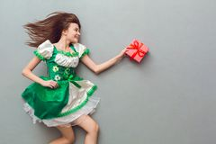 Young woman in a festive dress saint patrick`s day top view holding gift box. Young woman wearing a festive dress saint patrick`s day  on grey top view profile Stock Images