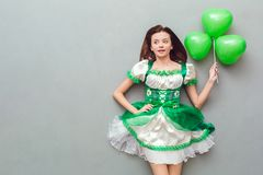 Young woman in a festive dress saint patrick`s day top view holding balloon. Young woman wearing a festive dress saint patrick`s day isolated on grey top view Stock Images