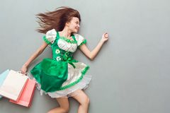 Young woman in a festive dress saint patrick`s day top view walking with shopping bags. Young woman wearing a festive dress saint patrick`s day isolated on grey Stock Photos