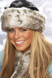 Young Woman Wearing Fur Hat And Wrap In Studio. Fashionable Young Woman Wearing Fur Hat And Wrap In Studio With Artificial Christmas Tree Stock Photography