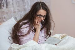 Young woman wearing glasses while reading book in bed. Relaxed woman lying in bed in sleepwear reading a book. Young woman wearing glasses while reading book in Stock Photo