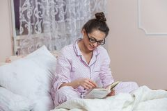 Young woman wearing glasses while reading book in bed. Relaxed woman lying in bed in sleepwear reading a book. Young woman wearing glasses while reading book in Stock Photography