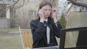 Young woman wearing glasses while sitting at the keyboard instrument outdoors. Notebook with notes is on a stand in. Young confident woman wearing glasses while stock video footage