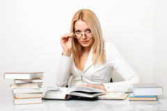 Young woman wearing glasses at table with books Stock Photography