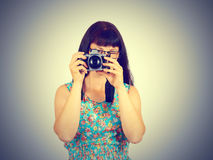Young woman wearing glasses taking pictures on the retro camera Stock Images