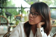 Young woman wearing glasses thinking and waiting someone in coff. Young asia woman wearing glasses thinking and waiting someone in coffee cafe. image for people Stock Images