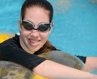 Young woman wearing goggles. Teenage girl in a swimming pool on a floating cushion Stock Photo