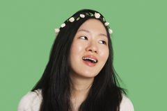 Young woman wearing hair ornament looking away over green background Stock Photo
