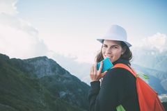 Young woman wearing a hat and backpack using mobile phone, sitting high in beautiful mountain reserve at sunset. Outdoors Stock Photography