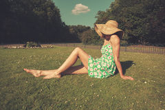 Young woman wearing hat and dress sitting in park Royalty Free Stock Photo