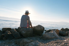 Young woman wearing hat, looking at beautiful view of sea Stock Images
