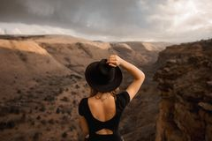 Young woman wearing hat standing by the canyonand mountain royalty free stock image