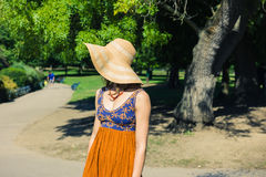 Young woman wearing hat standing in the park stock photography