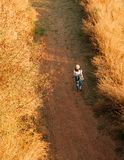 Young woman wearing hat walking on dirt road in dried grass field enjoy nature in evening stock photography