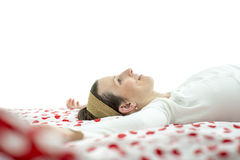 Young woman wearing a headband lying resting on a bed Royalty Free Stock Photos