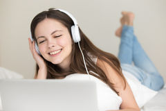 Young woman wearing headphones listening music on laptop at home Stock Images
