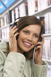 Young woman wearing headphones, listening to CDs in record shop, smiling, close-up Royalty Free Stock Image