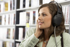 Young woman wearing headphones, listening to CDs in record shop, smiling, close-up, side view Stock Image