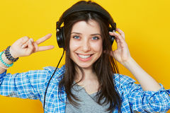 Young woman wearing headphones over bright yellow background. Stock Images