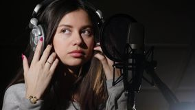 Young woman wearing headphones in recording studio near microphone royalty free stock photography