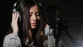 Young woman wearing headphones in recording studio near microphone Royalty Free Stock Images