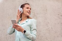 Young woman in headphones standing isolated on wall with smartphone listening music looking aside joyful stock photos