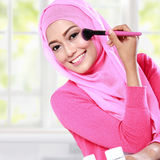 Young woman wearing hijab applying blush on Royalty Free Stock Photo